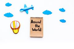 Family trip concept. Airplan toy, air balloon cookie. Around the world hand lettering in notebook on white background. Top view Royalty Free Stock Photography