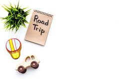 Family trip concept. Green plant, air ballon cookie, car toy. Road trip hand lettering in notebook on white background Stock Photography