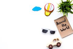 Family trip concept. Sun glasses, green plant, air ballon cookie, car toy. Around the world hand lettering in notebook Stock Photo