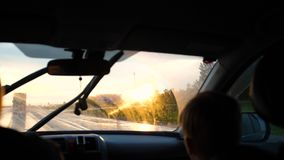 Family trip. The family goes by car on the highway. Sunset time. The movement of the car on the highway stock video