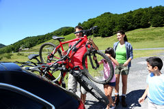 Family on a trip going riding bikes. Family preparing bicycles for recreational journey Royalty Free Stock Image