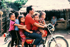 Family trip. A Hmong man and five children cruising through a refugee camp in northern Thailand, 1984 Stock Photography