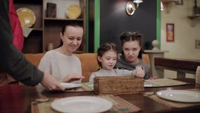 Mom with her two daughters talking in the cafe while the waiter puts on the table Cutlery. Family trip to the cafe. mom with her two daughters talking in the stock video footage