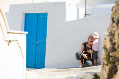 Family trip to Europe. Young mother with two kids exploring Greek town Royalty Free Stock Photography