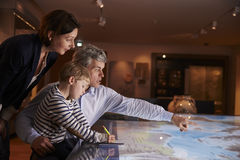 Family On Trip To Museum Looking At Map Together Royalty Free Stock Image