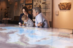 Family On Trip To Museum Looking At Map Together Royalty Free Stock Photos
