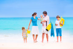Family on a tropical beach. Beautiful young family with three children, happy boy, cute toddler girl and a little baby walking together on a tropical island Royalty Free Stock Image