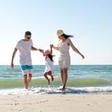 Family on tropical beach. Family of three having fun on tropical beach Royalty Free Stock Images