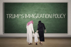Family with Trump`s Immigration Policy word. Muslim family walking together in the classroom with Trump`s Immigration Policy word on the chalkboard stock photos