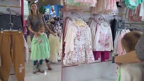 Family try on wear clothing in the shop. Mother with daughter choosing clothes in the shopping mall. Happy family buying in emporium. Adult caucasian lady with stock video footage