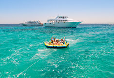 Family on tube in water being towed by boat. Royalty Free Stock Photo