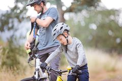 Family of two biking. Family of two, young father and cheerful son, enjoying bike riding, active family concept Royalty Free Stock Images