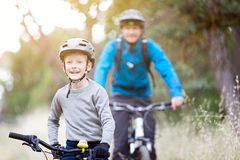 Family of two biking. Family of two, young father and cheerful son, enjoying bike riding, active family concept Royalty Free Stock Photo