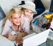 Family of two buying tickets online. Happy young mother with little daughter buying online tickets for long-awaited vacation Stock Photos
