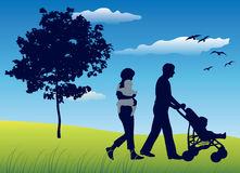 Family with two children and carriage walking on field. Near tree, blue sky Stock Image