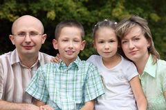 Family with two children in early fall park. Royalty Free Stock Image