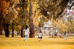 Family with two children flying a kite and running across grassy lawn. In autumn park royalty free stock images
