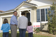Family with two children (6-8) in front of new house back view Stock Photography