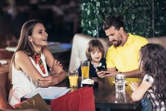 Family with two children having great time in a cafe after shop. Ping, having fun royalty free stock image