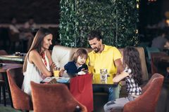 Family with two children having great time in a cafe after shop. Ping, having fun stock image
