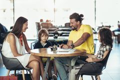 Family with two children having great time in a cafe after shop. Ping, having fun royalty free stock photography