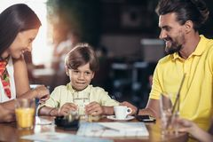 Family with two children having great time in a cafe after shop. Ping, having fun royalty free stock photo