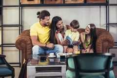 Family with two children having great time in a cafe after shop. Ping, having fun stock images