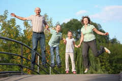 Family with two children is jumping on a bridge stock photo