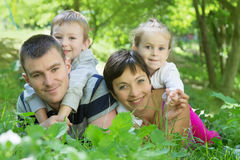 Family with two children lying down in the park Royalty Free Stock Images