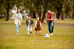 Family with two children playing football together in an. Autumn park stock photos