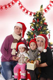 Family with two children posing under Christmas tree. Happy family with two children posing under Christmas tree Stock Image