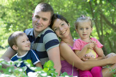 Family with two children sitting in the grass Royalty Free Stock Photography