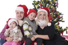 Family with two children sitting under Christmas tree. Happy family with two children sitting under Christmas tree over white Royalty Free Stock Photography