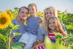 Family with two children in sunflower field Stock Photo
