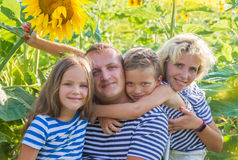 Family with two children in sunflower field Stock Photos