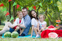 Family with two children on watermelon picnic outdoor Royalty Free Stock Image