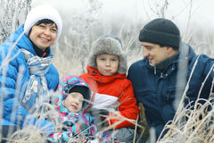 Family with two children in winter field Stock Images