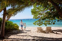Family of two at vacation. Family of two, father and son, running on empty beautiful white sand beach with palm trees and turquoise lagoon, family vacation Stock Photos