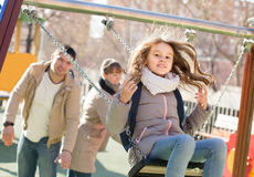 Family with two girls having fun on swings outdoors stock photo