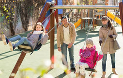 Family with two girls having fun on swings outdoors Royalty Free Stock Image