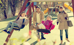 Family with two girls having fun on swings outdoors Royalty Free Stock Photos