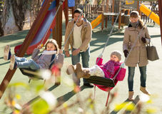Family with two girls having fun on swings outdoors Stock Images