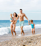 Family with two kids on beach Stock Photos