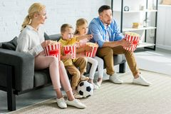 family with two kids eating popcorn and watching tv royalty free stock image