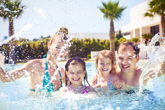 Family with two kids having fun in the swimming pool Stock Photos