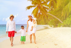 Family with two kids walking at tropical beach Stock Photo