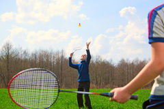 Family - two little boys playing badminton. On green meadow Royalty Free Stock Image