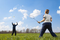 Family - two little boys playing badminton. On green meadow Royalty Free Stock Photo