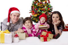 Family with two little daughters lying under Christmas tree royalty free stock photos