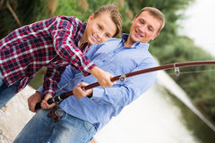 Family of two people fishing together on freshwater lake. Happy family of two people fishing together on freshwater lake from shore Royalty Free Stock Photo
